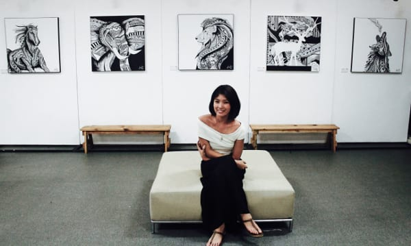 Kara Pangilinan smiling while sitting in front of her pen and ink artworks