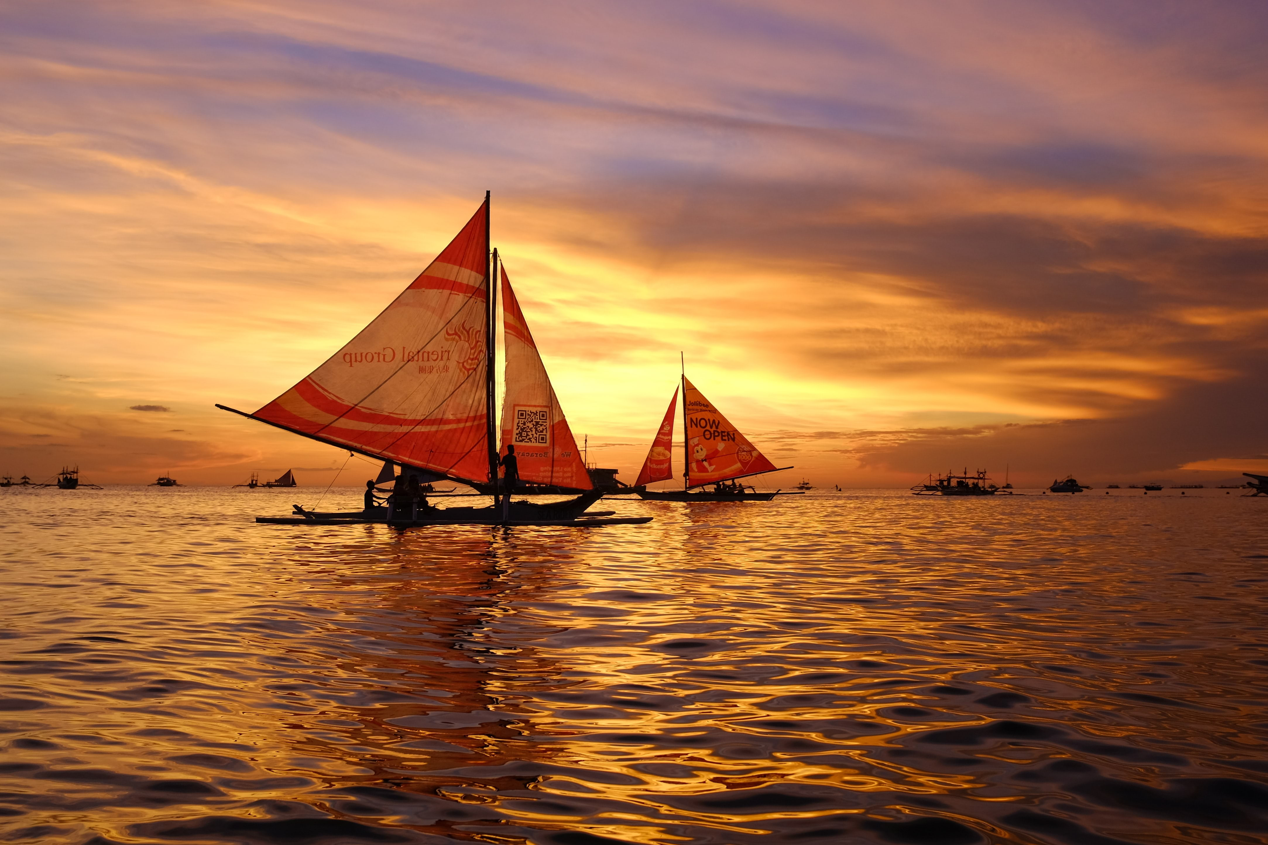 silhouette of sail boats floating on body of water