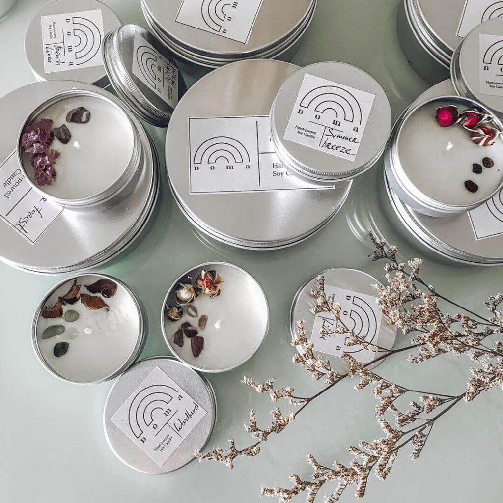 Doma's candles in small and large tin cans